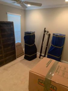 Room filled with fully packed boxes and wrapped furniture